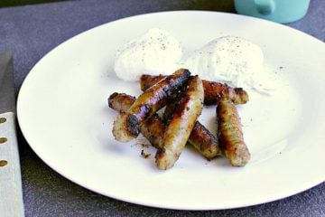 plate with maple breakfast sausages and two poached eggs.