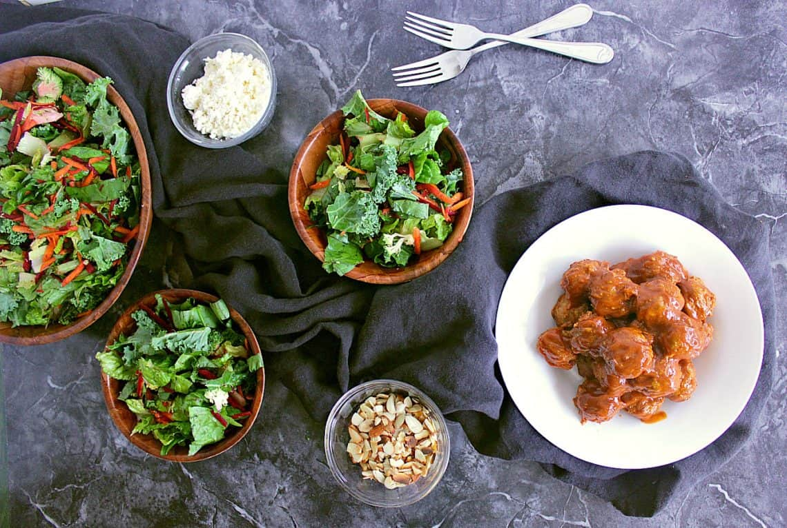 Bowl of mini meatballs smothered in low carb bbq sauce, next to three salads, sliced almonds and feta cheese.