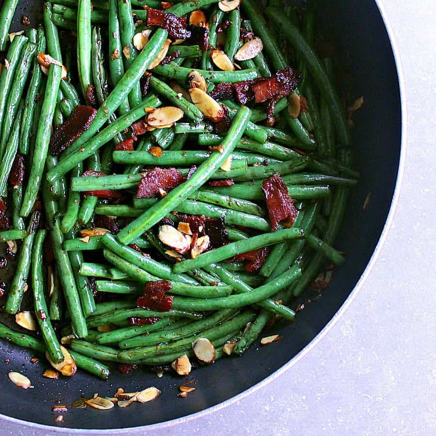 Deep dish frying pan filled with green beans, bacon and almonds.