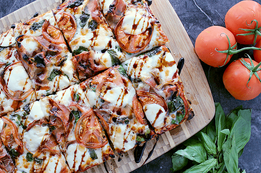 Pizza sliced up and drizzled with balsamic glaze.