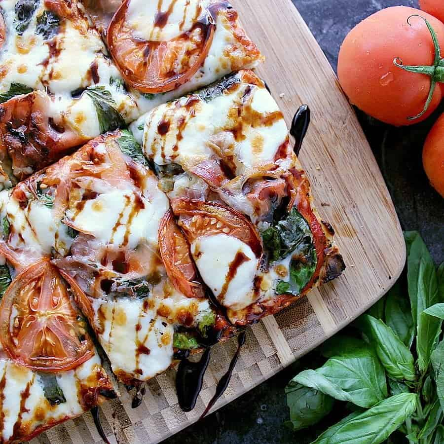 Homemade Focaccia Pizza with Prosciutto, Basil and Bocconcini, sliced into rectangles and drizzled with balsamic reduction.