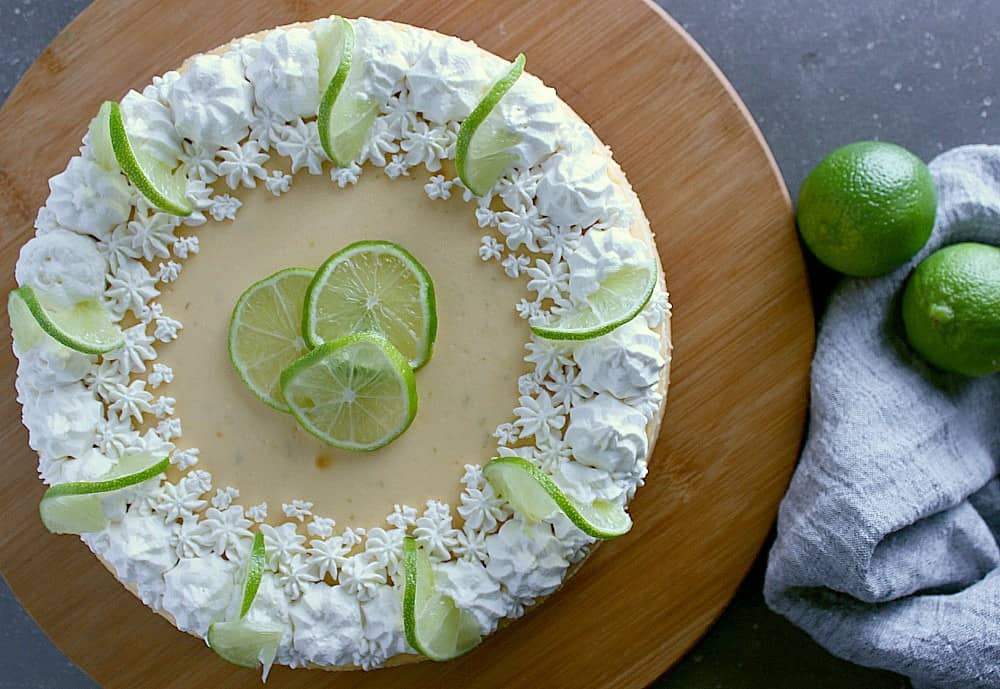 Top of the lime cheesecake, displaying fresh whipped cream and lime slices.