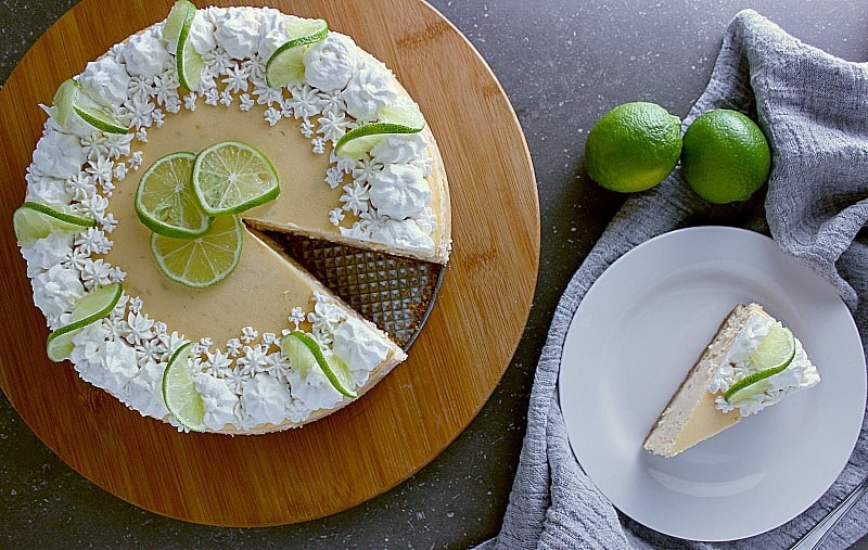 Top of the lime cheesecake decorated with fresh whipped cream and lime slices. One slice is removed and served on a plate.