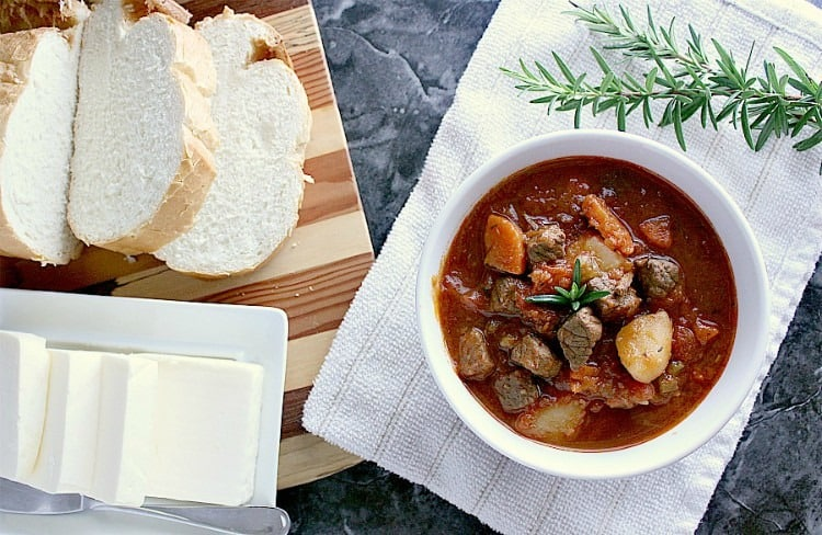 Bowl of Instant Pot Beef Stew, garnished with fresh rosemary, next to a platter with a sliced Italian loaf and some butter.