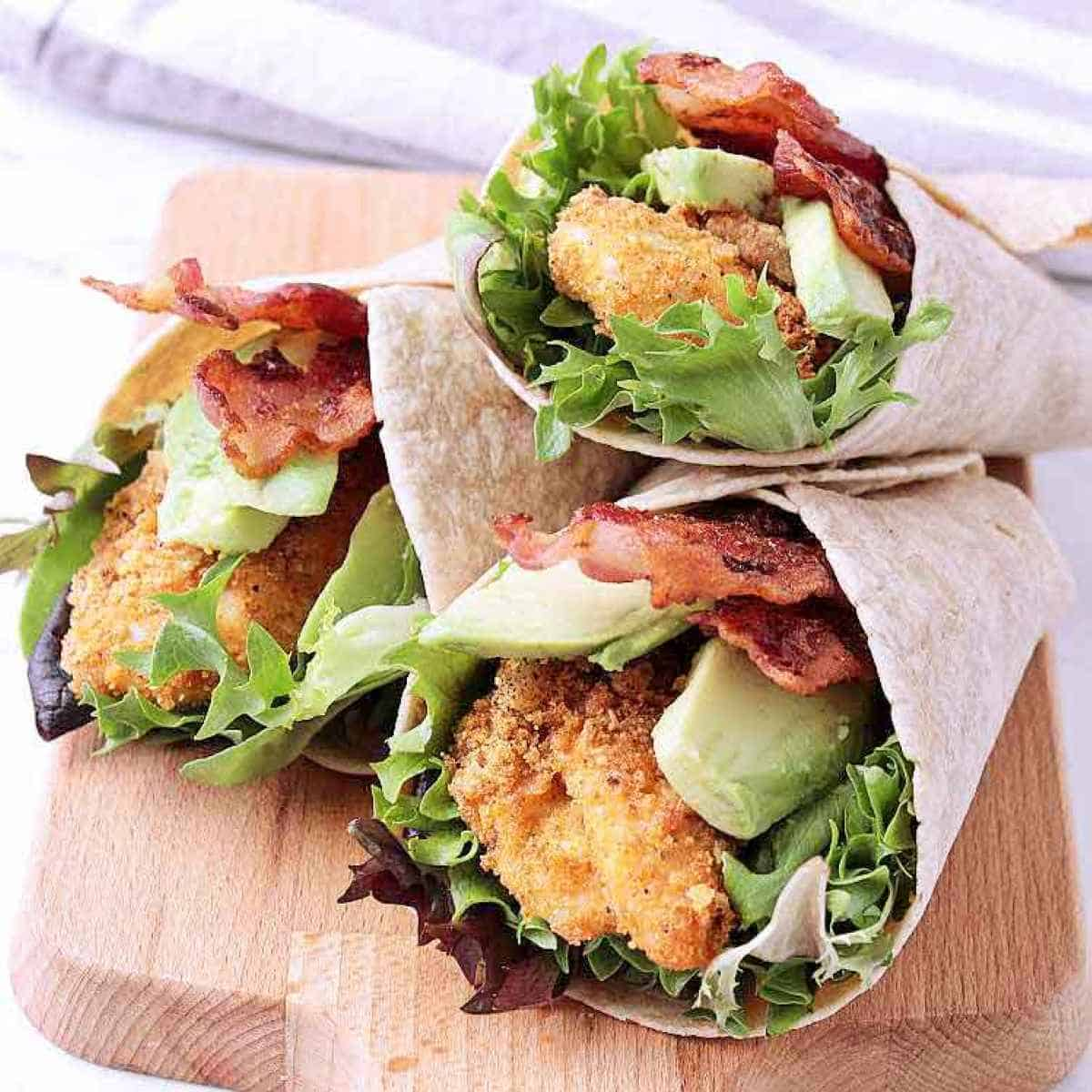 Low Carb Chicken Wrap loaded with bacon and avocado, sliced in half to show the inside goodies.