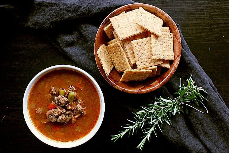 Bowl of low carb crackers next to a bowl of beef vegetable soup and a couple of fresh sprigs of rosemary.