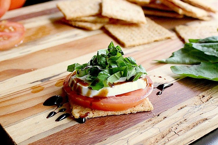Low Carb Cracker topped with a slice of tomato, slice of bocconcini, freshly chopped basil and a balsamic reduction.