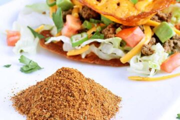 A pile of keto taco seasoning in front of two keto tacos.
