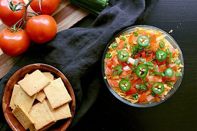 Birds eye view of the mexican low carb 7 layer dip, next to some fresh tomatoes and crunchy low carb cheese crackers.