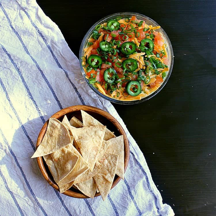A bowl of low carb baked tortilla chips next to a low carb 7 layer dip.