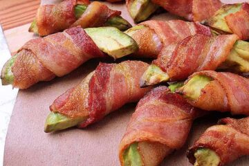 Pile of bacon wrapped avocado fries, beside a dish of ranch dip.