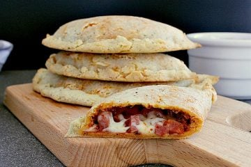 Stack of keto calzones with a half calzone cut in half to show the meat and cheese inside.