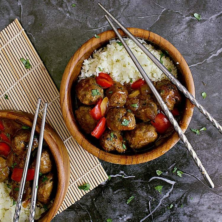 Two wooden bowls of keto sweet and sour meatballs with cauliflower rice.