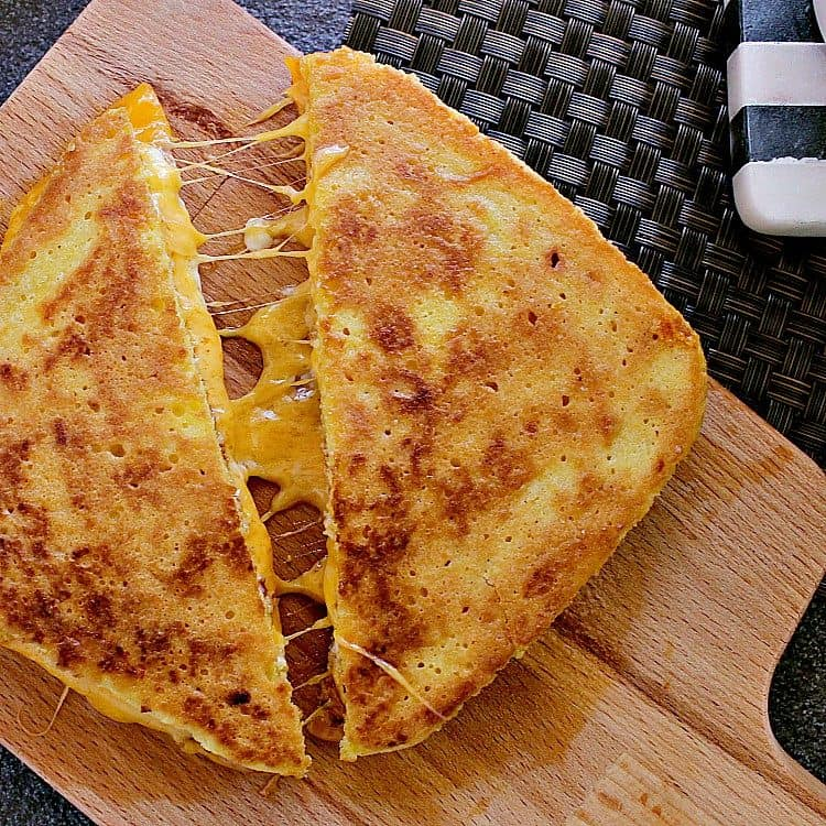 Keto Grilled Cheese cut in half, halves slightly pulled apart to show the melty gooey cheese.