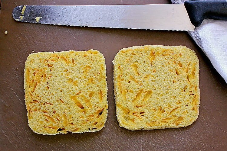 Cooked bread, sliced in half, both slices laying on a cutting board, ready to be fried.