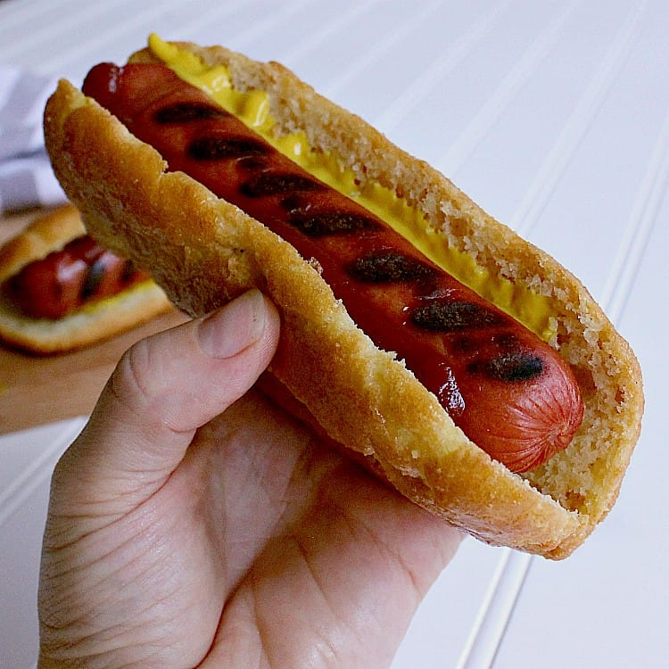 Hot dog in a keto hot dog bun with ketchup and mustard.