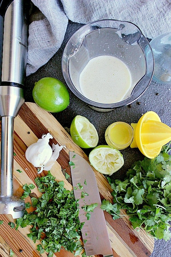Dressing whipped up using an immersion blender, next to a cutting board filled with minced cilantro.