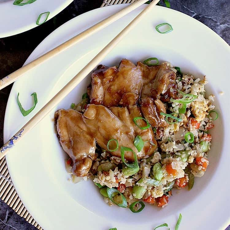 Plate with keto fried rice and low carb honey garlic chicken thighs.