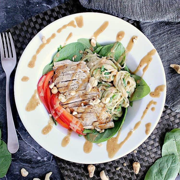 Salad bowl with Low Carb Thai Salad, covered in extra peanut sauce and chopped cashews.