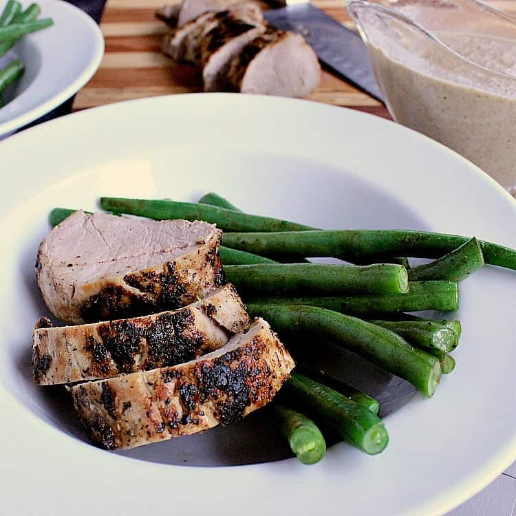 Plate of green beans with three slices of pork tenderloin. The plate is next to the remaining sliced pork and mushroom sauce.