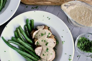 Plate with green beans and sliced pork loin, covered in mushroom sauce.