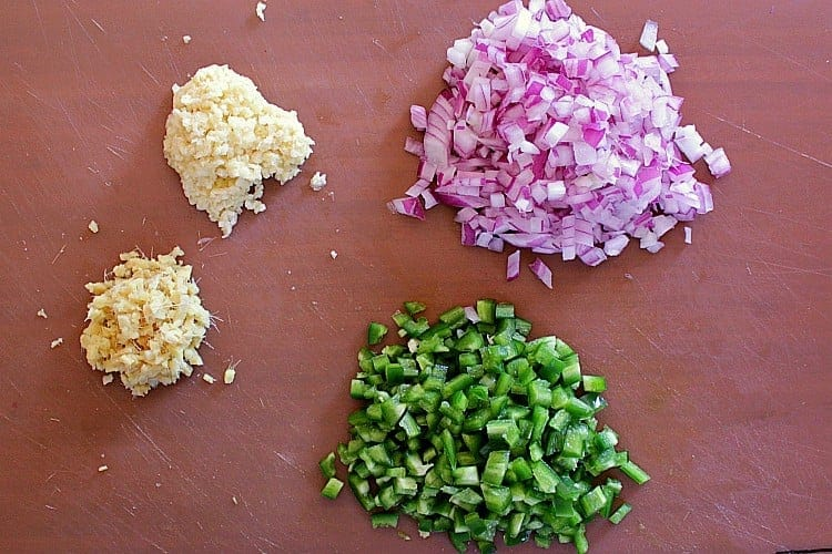 Cutting board with minced garlic and ginger, and diced red onion and jalapenos.