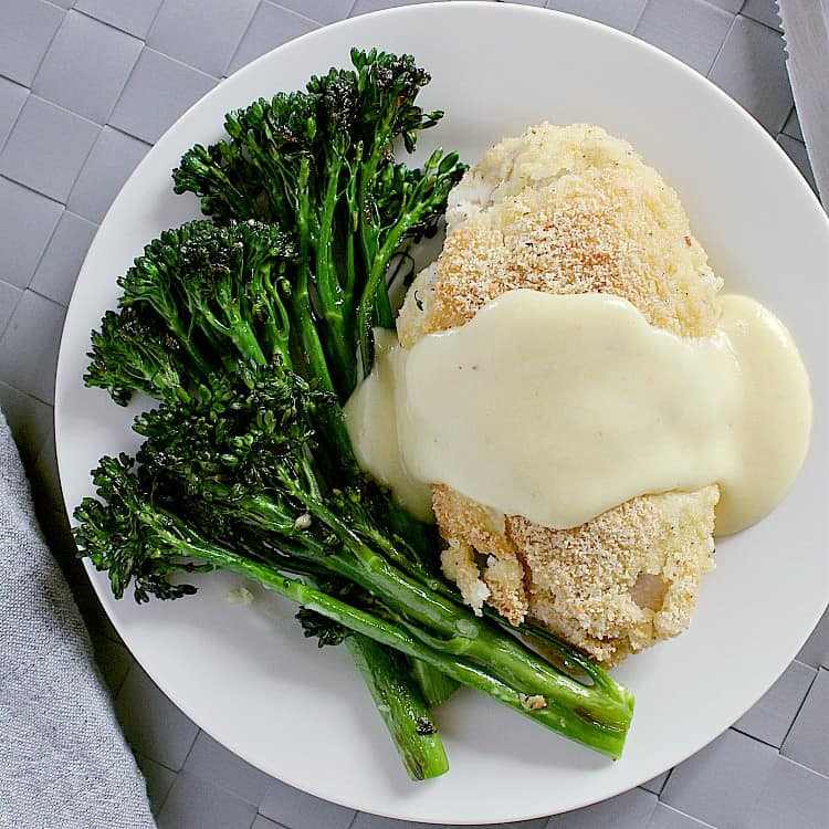 Keto chicken cordon bleu on a plate with garlic sauteéd broccolini and covered with keto cheese sauce.