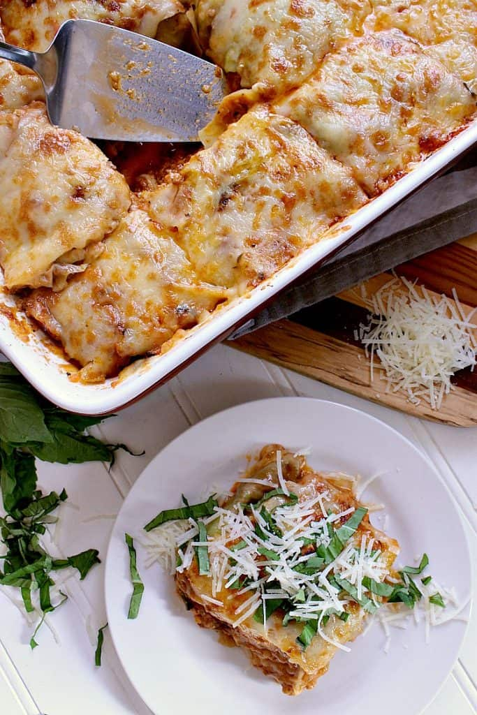 Baking dish with freshly baked low carb cabbage lasagna, one slice is on a plate with freshly grated parmesan cheese and basil.