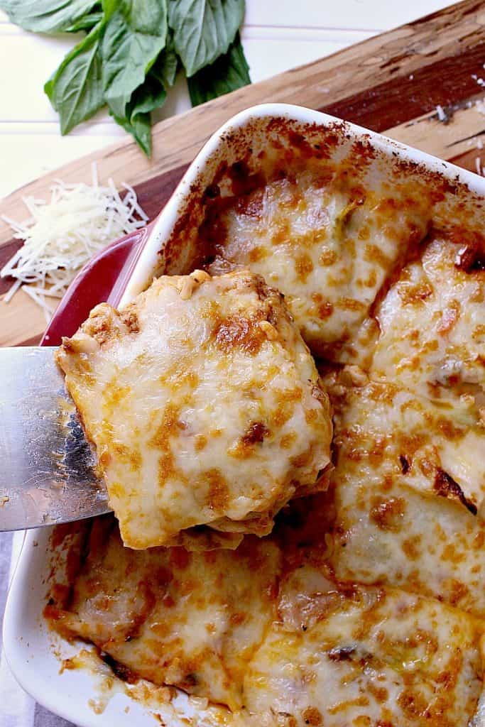 Baking dish with freshly baked low carb cabbage lasagna, one slice is being removed.