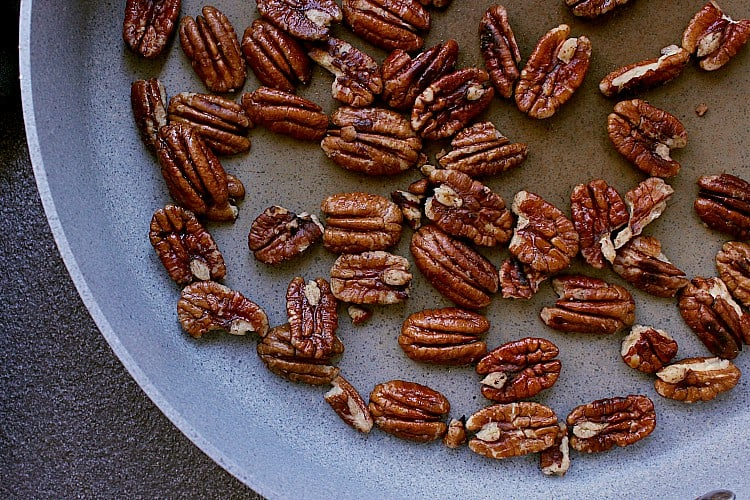 Skillet full of warmed pecans.