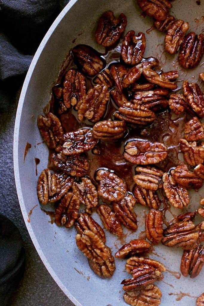 Skillet full of candied pecans, ready to be transferred to a baking sheet to cool completely.