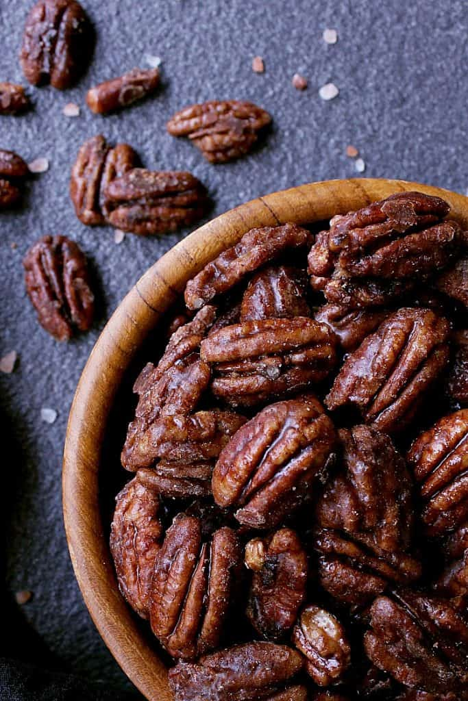 Wooden bowl with sugar free candied pecans on a stone surface.