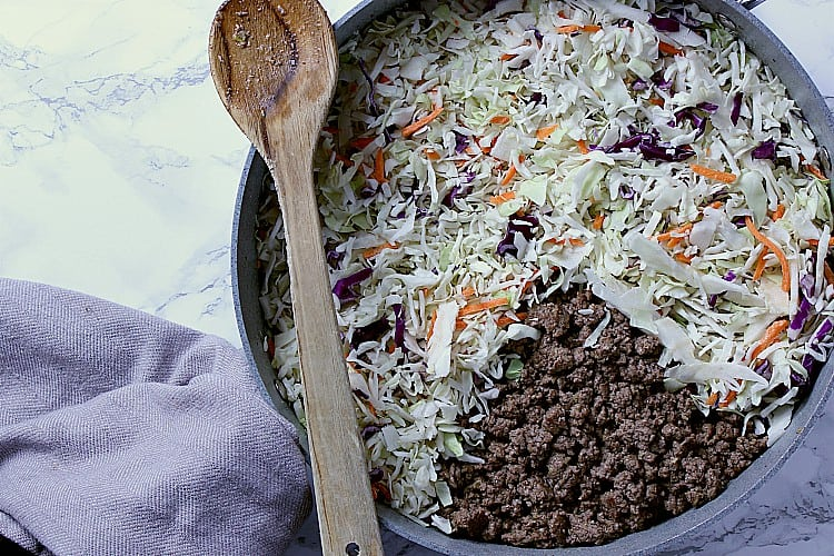 Skillet with cooked beef, slaw has just been added.