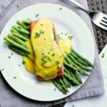 Plate with steamed asparagus and salmon, covered in keto hollandaise sauce and garnished with chives.