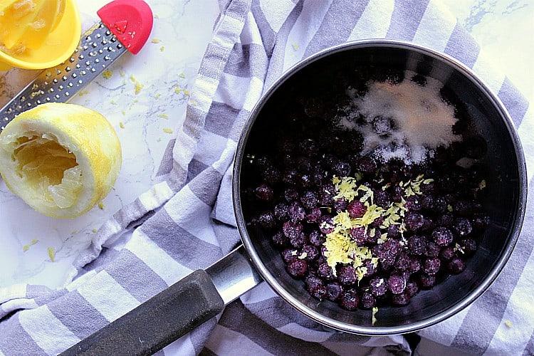 Saucepan with blueberries, lemon zest and sweetener.