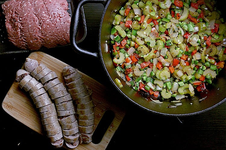 Fried veggies in a cast iron dutch oven beside sliced sausages and ground beef.
