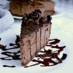 A slice of keto chocolate cheesecake garnished with extra chocolate drizzle and shaved dark chocolate.