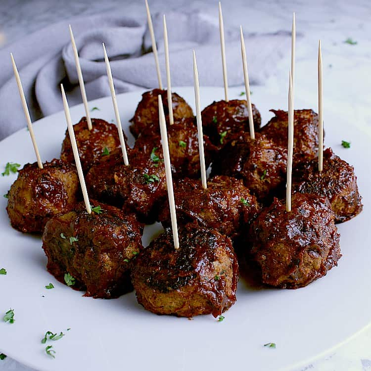 Platter of bbq keto meatballs, each with a toothpick, ready to be served as an appetizer.