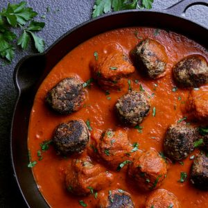 Cast iron skillet with cooked meatballs, hot marinara sauce and garnished with fresh parsley.