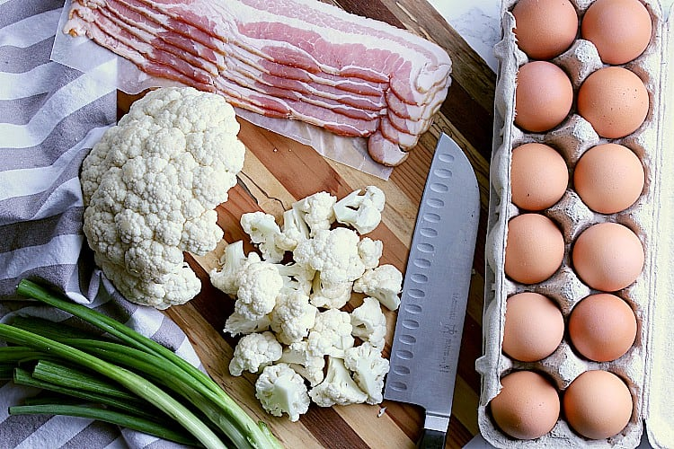 Cutting board with cauliflower, green onion, carton of eggs and some bacon.