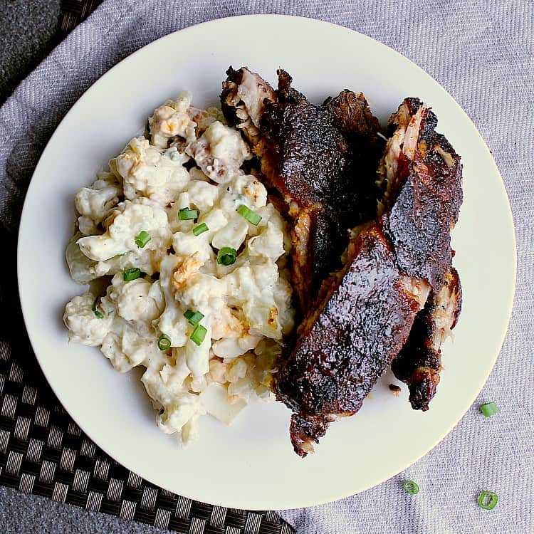 Plate with cauliflower potato salad with some low carb ribs.