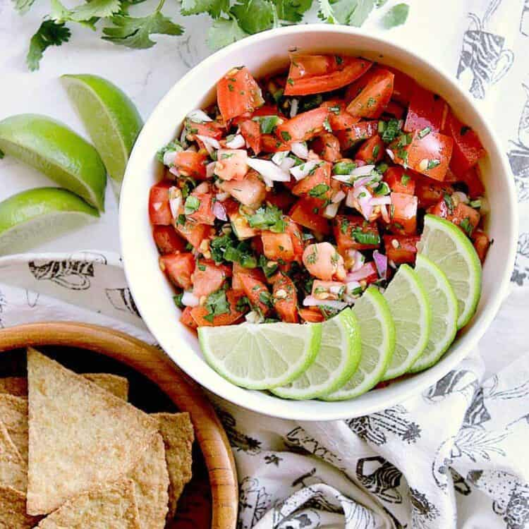 A white bowl with Keto pico de gallo, and sliced limes on top, next to a bowl of Keto chips.