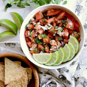 Bowl of keto pico de gallo garnished with fresh lime slices, besides a bowl of low carb baked tortilla chips.