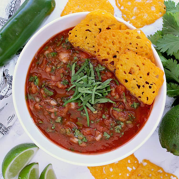 Bowl of keto salsa garnished with cilantro and cheese crisps.