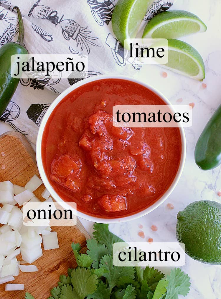 Bowl of diced tomatoes surrounded by limes, jalapeños, diced onion and cilantro.