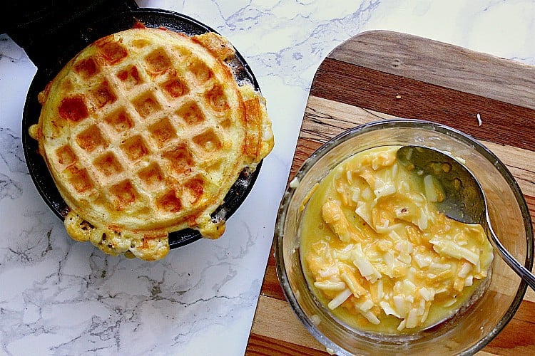 First keto chaffle is cooked, next to a dish with the remaining egg mixture.