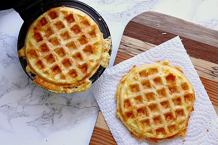 Both chaffles are ready, one on a cutting board and the other is in the open waffle maker.