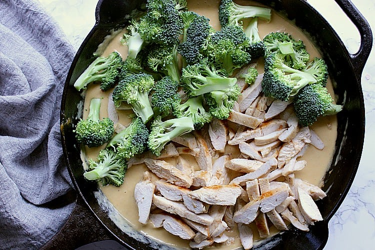 Skillet with alfredo sauce and chicken and broccoli dumped on top.