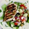 A white bowl with chopped romaine, greek salad and a piece of grilled keto greek chicken.