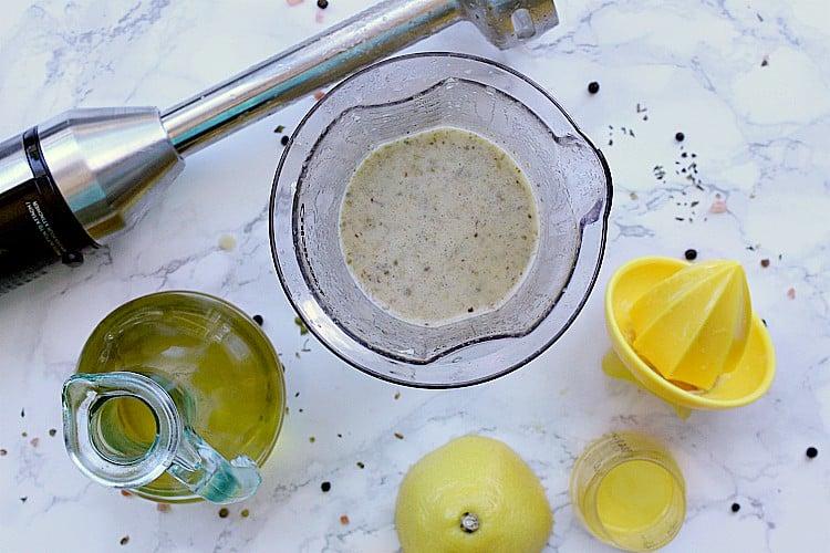 Cup of dressing beside an immersion blender, olive oil and lemon juicer.